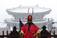 An Imperial guard wearing a face mask stands in the snow outside the Gyeongbok Palace, the main royal palace during the Joseon Dynasty in Seoul, South Korea, on Feb. 17, 2020. (AP Photo/Ahn Young-joon)