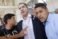 Opposition leader Juan Guaido is escorted after he was drenched by supporter of President Nicolas Maduro, as arrives to the Simon Bolivar International Airport in La Guaira, Venezuela, on Feb. 11, 2020. (AP Photo/Ariana Cubillos)