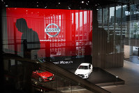 In this July 25, 2019, file photo, a man rides an escalator as Nissan vehicles are showcased in the Nissan Gallery in Yokohama. (AP Photo/Jae C. Hong)
