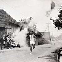日の丸を振る沿道の住民らの声援を受けて走る松村賢剛さん=福島県日和田町(現郡山市日和田町)で1964年9月29日(松村さん提供)