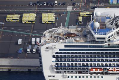 横浜港に停泊するクルーズ船「ダイヤモンド・プリンセス」付近に待機するバス(左上)=横浜市鶴見区で2020年2月19日午前10時40分、本社ヘリから