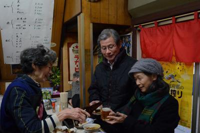 客と笑顔で話す店主の平尾ユカリ(左)さん(左)=北九州市小倉北区の平尾酒店で
