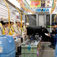 試験車両内に置かれた機器を見つめるJR西日本の社員ら=大阪市内で2020年2月18日、山田尚弘撮影