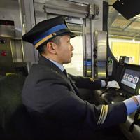 自動運転を行う運転士。緊急時に備え、レバー類に手を添えている=大阪市内で2020年2月18日、山田尚弘撮影