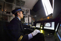 A train driver is seen on standby in the driving seat for a train being driven automatically in Osaka on Feb. 18, 2020. His hands remain on the levers in case of an emergency. (Mainichi/Naohiro Yamada)