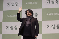 Bong Joon-ho, director of Oscar-winning film 'Parasite,' waves after a press conference in Seoul, South Korea, on Feb. 19, 2020. (AP Photo/Ahn Young-joon)
