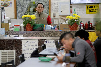 In this Feb. 13, 2020, photo, restaurant owner Phong Nguy watches from his counter as customers eat lunch in the food court at the Mekong Plaza in the Asian district, in Mesa, Ariz. (AP Photo/Matt York)