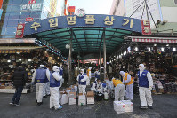 In this Feb. 5, 2020, file photo, workers wearing protective gears prepare to spray disinfectant as a precaution against a new coronavirus at Namdaemun Market in Seoul, South Korea. (AP Photo/Ahn Young-joon)
