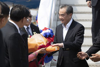 China's Foreign Minister Wang Yi, right, arrives at Wattay International Airport in Vientiane, Laos, on Feb. 19, 2020. (AP Photo/Sakchai Lalit)