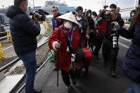 An unidentified passenger is surrounded by the media after she disembarked from the quarantined Diamond Princess cruise ship on  Feb. 19, 2020, in Yokohama, near Tokyo. (AP Photo/Jae C. Hong)
