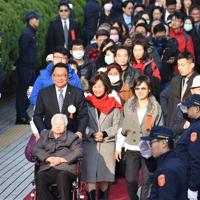 母親の乗った車椅子を押しながら、大勢の親族らと初登院する民進党の陳欧珀氏=台湾立法院で1日