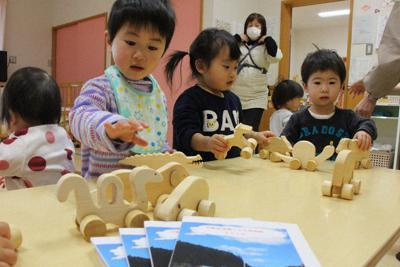 釣崎さんから届いた冊子(手前)と木のおもちゃで遊ぶ園児たち=岩手県陸前高田市竹駒町の竹駒保育園で