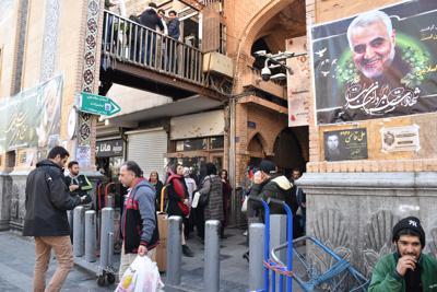 大勢の客でごった返すグランドバザール入り口に掲げられたソレイマニ司令官の肖像=テヘランで2020年2月18日、山本太一撮影