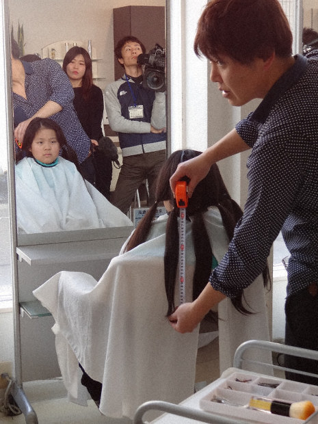 An employee at the hair salon Takita in the city of Joetsu, Niigata Prefecture, checks to confirm that Mitsuhiro Hao's hair measures 31 centimeters in length, on Feb. 11, 2020. (Mainichi/Shigeharu Asami)