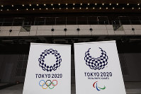 In this Feb. 2, 2020, file photo, two logos for the Tokyo 2020 Olympics and Paralympics, are displayed at a grand opening ceremony of the Ariake Arena, a venue for volleyball at the Tokyo 2020 Olympics and wheelchair basketball during the Paralympic Games, in Tokyo. (AP Photo/Jae C. Hong)