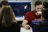 In this Feb. 13, 2020 photo, Kyle Martin, a worker at HealthMap, a system using artificial intelligence to monitor global disease outbreaks, mines health data to keep the system up to date in a work area at Boston Children's Hospital in Boston. (AP Photo/Steven Senne)