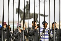 Tourists take pictures during the Kremlin guards is changing with the monument of Soviet Marshal Georgy Zhukov in the background in Manezhnaya Square near the Kremlin in Moscow, Russia, on Feb. 19, 2020. (AP Photo/Alexander Zemlianichenko)