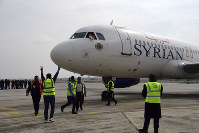 This photo released by the Syrian official news agency SANA, shows workers welcoming a Syrian commercial plane carrying Syrian officials and journalists after it landed at Aleppo Airport, Syria, on Feb. 19, 2020. (SANA via AP)