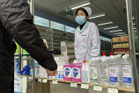 A pharmacy worker attends to visitors at the store entrance in Beijing, China, on Feb. 20, 2020. (AP Photo/Ng Han Guan)