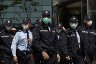 Police officers wearing masks, patrol in Central, a business district in Hong Kong, on Feb. 19, 2020. (AP Photo/Kin Cheung)