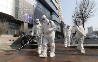Workers wearing protective gears spray disinfectant against the new coronavirus in front of a church in Daegu, South Korea, on Feb. 20, 2020. (Kim Jun-beom/Yonhap via AP)