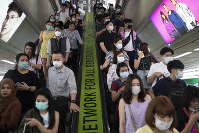 In this Feb. 7, 2020, file photo, commuters wear face masks to protect themselves from new virus at the skytrain station in Bangkok, Thailand. (AP Photo/Sakchai Lalit)