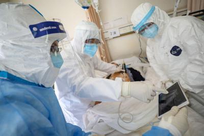 防護服に身を包んで患者を診る医療関係者=武漢市内の病院で2月16日、ロイター
