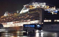 クルーズ船(奥)から下船した米国人を乗せて出発するバス=横浜市鶴見区で2020年2月17日、竹内紀臣撮影