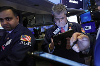 In this Feb. 5, 2020, file photo specialist Dilip Patel, left, and trader John Panin work on the floor of the New York Stock Exchange. (AP Photo/Richard Drew)