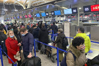 In this Jan. 30, 2020 file photo, travelers wearing face masks stand in line at the check-in counters for Cathay Pacific at Shanghai Pudong International Airport in Shanghai, China. (AP Photo/Erika Kinetz)