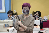 In this Feb. 17, 2020, photo, volunteers pose for a photo with their handmade cotton masks in Hong Kong. (AP Photo/Kin Cheung)