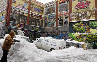 In this Jan. 26, 2011, file photo, a man shovels snow to clear a driveway near 5pointz, a graffiti art gallery in the Long Island City neighborhood of the Queens borough of New York. (AP Photo/Frank Franklin II)