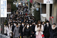 People wear masks on their commute during the morning rush hour on Feb. 20, 2020, in Tokyo's Chuo Ward. (AP Photo/Kiichiro Sato)