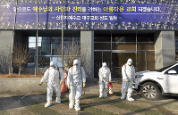 In this Feb. 19, 2020, photo, workers wearing protective gear spray disinfectant against the coronavirus in front of a church in Daegu, South Korea. (Lee Moo-ryul/Newsis via AP)