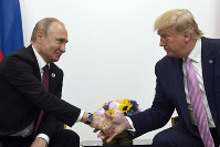 In this June 28, 2019, file photo, President Donald Trump, right, shakes hands with Russian President Vladimir Putin, left, during a bilateral meeting on the sidelines of the G-20 summit in Osaka, Japan.  (AP Photo/Susan Walsh)