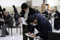 Voters with face masks fill out their ballots in the parliamentary elections at a polling station in Tehran, Iran, on Feb. 21, 2020. (AP Photo/Vahid Salemi)