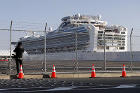 A photographer takes photos near the quarantined Diamond Princess cruise ship anchored at a port in Yokohama, near Tokyo, on Feb. 21, 2020. (AP Photo/Eugene Hoshiko)