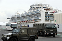 A bus carrying passengers from the quarantined Diamond Princess cruise ship escorted by Japan Self Defense Forces vehicles leaves a port in Yokohama, near Tokyo, on Feb. 20, 2020. (AP Photo/Eugene Hoshiko)
