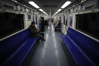 Commuters ride in a quiet subway train during the morning rush hour in Beijing, on Feb. 17, 2020. (AP Photo/Andy Wong)