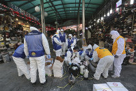 In this Feb. 5, 2020 photo, workers wearing protective gear prepare to spray disinfectant as a precaution against the coronavirus at Namdaemun Market in Seoul, South Korea. (AP Photo/Ahn Young-joon)