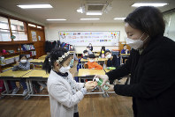 In this Jan. 30, 2020 file photo, a teacher dispenses hand sanitizer to a student at Yongsan elementary school in Seoul, South Korea. (Park Dong-ju/Yonhap via AP)