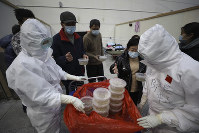 In this Feb. 21, 2020 photo, nurses in protective suits distribute meals to patients at a temporary hospital at Tazihu Gymnasium in Wuhan in central China's Hubei province. (Chinatopix via AP)