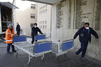 Personnel carry new beds inside the hospital of Codogno, near Lodi in Northern Italy, on Feb. 21,2020. (AP Photo/Luca Bruno)
