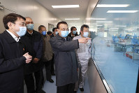 In this Feb. 21, 2020 photo released by China's Xinhua News Agency, Chinese Premier Li Keqiang, second from right, visits a mask production line at a medical supply company in Beijing. (Ding Lin/Xinhua via AP)