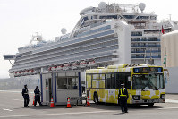 A bus carrying passengers from the quarantined Diamond Princess cruise ship leaves a port in Yokohama, near Tokyo, on Feb. 20, 2020. (AP Photo/Eugene Hoshiko)