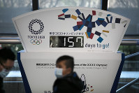 Two people wearing masks sit in front of a countdown clock for the Tokyo 2020 Olympics on Feb. 18, 2020, in Tokyo. (AP Photo/Jae C. Hong)