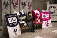 A woman removes her mask before taking pictures with the mascots of the Tokyo 2020 Olympics and Paralympics, in Tokyo, on Feb. 18, 2020. (AP Photo/Jae C. Hong)