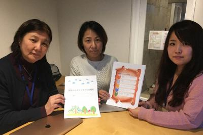 プログラムで使用した冊子を紹介する(左から)井上匡子教授、高田恭子准教授、協力した光本歩さん=東京都内で