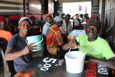 バケツに入ったムコンボティを飲む男性客ら=南アフリカのソウェトで2020年1月31日午後4時17分、小泉大士撮影