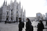 People wearing sanitary masks walk past the Duomo gothic cathedral in Milan, Italy, on Feb. 23, 2020. (AP Photo/Luca Bruno)